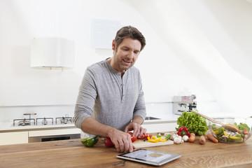 Deutschland, München, Mann Zubereitung von Speisen, während Sie Tablet PC anschaut