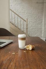 Croissant auf dem Tisch mit Getränken und Laptop