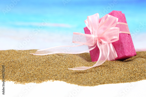 Gift box with ribbon on the sand