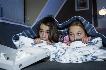 Mädchen, Gesicht mit Bettlaken zudecken, während Sie beängstigend Film anschauen