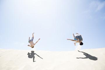 Frankreich, Zwei Jungen springen auf Sanddüne