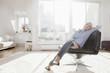 Deutschland, München, Frau entspannt auf Stuhl im Wohnzimmer