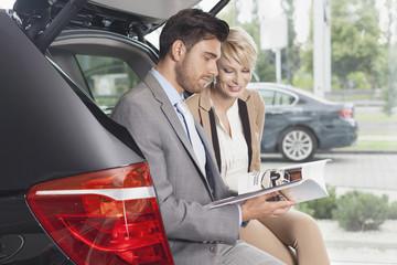 Beim Autohändler, Paar liest Katalog, Kofferraum