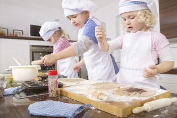 Deutschland, Mädchen und Jungen cup cake backen und Gießen Zuckerstreusel