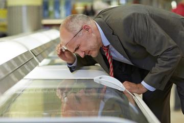 Deutschland, Köln, Mann suchen bei Gefrierfach im Supermarkt