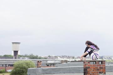 Deutschland, Hamburg, Junge Frau sitzt am Kamin