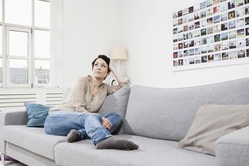 Deutschland, München, Frau sitzen auf der Couch und schaute weg