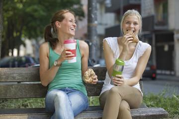 Deutschland, Köln, Junge Frauen sitzen auf der Bank mit Kaffee und Croissants