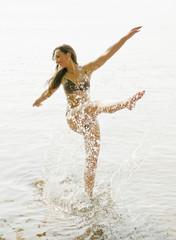 Deutschland, Brandenburg, Junge Frau spritzt Wasser im See
