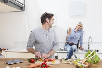 Deutschland, München, Mann schneidet Gemüse, Frau sitzt im Hintergrund