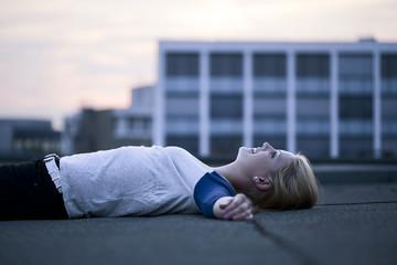 Junge Frau liegt auf Flachdach