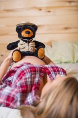 USA, Texas, Schwangere junge Frau mit Teddybär auf dem Bauch