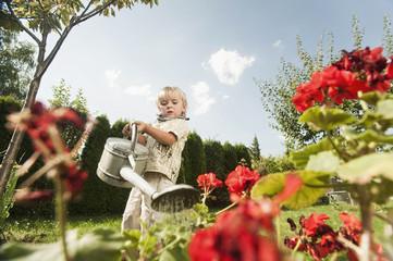 Deutschland, Bayern, Junge gießt Blumen