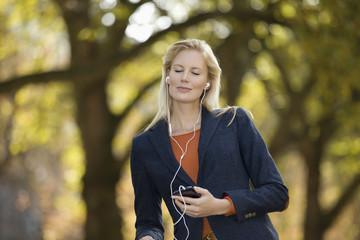Deutschland, Düsseldorf, junge Frau hört Musik mit Smart Phone