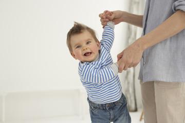 Lächeln Baby Jungen Hand in Hand mit seiner Mutter