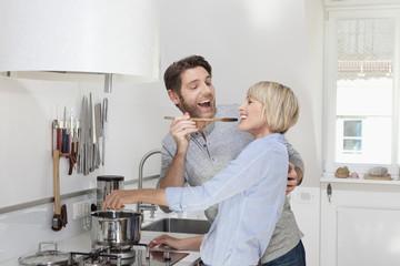 Deutschland, München, Seniorin, Kochen von Essen, während der Mann Mensch probieren lässt
