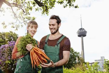 Deutschland, Köln, Junges Paar mit Bund Karotten