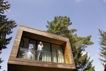 Deutschland, Berlin, Mann stehen auf dem Balkon mit Handy