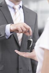 Beim Autohändler, Verkäufer übergeben Autoschlüssel Kunden