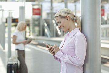 Deutschland, Düsseldorf, Geschäftsfrau mit Mobiltelefon, eine andere Frau liest Zeitung im Hintergrund