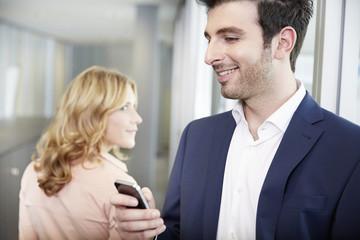 Deutschland, Frau schaut Mann an, mit Handy