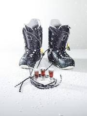 Snowboard -Schuhe mit Getränk auf weißem Hintergrund