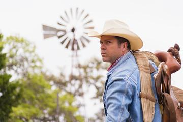 Texas, Cowboy mit Sattel und Ranch- Windmühle im Hintergrund
