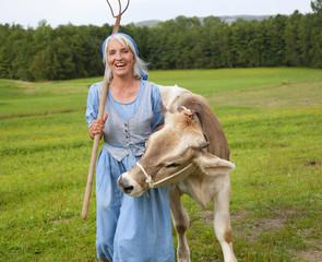 Deutschland, Bayern, Seniorin mit Kuh auf dem Bauernhof