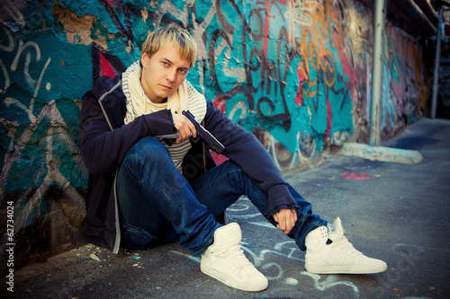 Blond teenager with a pistol sitting near graffiti wall