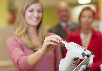Deutschland, Köln, Frau nutzt Kreditkarte im Supermarkt