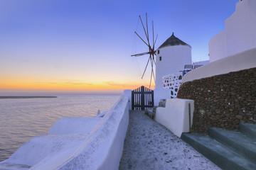 Griechenland, Blick auf Oia Dorf mit traditionellen griechischen Windmühlen im Sonnenuntergang auf Santorini