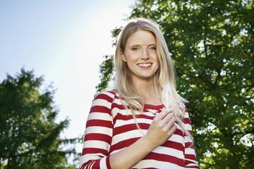 Deutschland, Köln, Junge Frau, hält Glühbirne