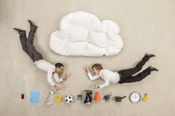 Geschäftsleute zwischen Wolke Form Kissen und Vielfalt der Einzelteile fliegen