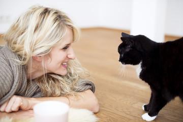 Junge Frau mit Katze auf Boden