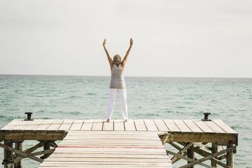 Spanien, Seniorin, Übungen auf Bootssteg am Meer