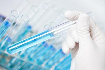 Deutschland, Menschliche Hand halten Reagenzglas mit blauer Flüssigkeit