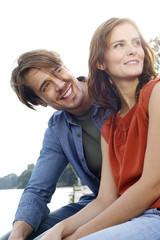 Deutschland, junge Paar sitzt am Seeufer