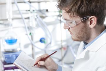 Deutschland, junger Wissenschaftler, notieren Anmerkungen ins Buch