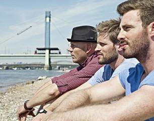 Deutschland, Köln, junge Männer sitzen am Flussufer