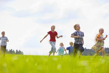 Deutschland, Bayern, Gruppe von Kindern rennen durch Wiese