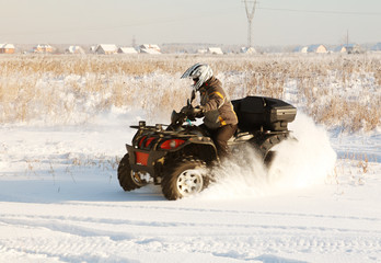 terrain vehicle in motion at winter sunny day