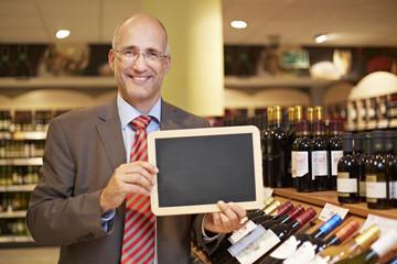 Deutschland, Köln, Mann halten Tafel im Supermarkt