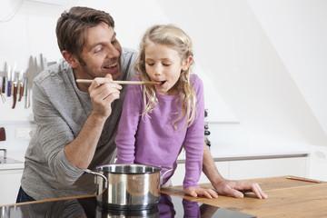 Deutschland, München, Vater lässt Tochter probieren in Küche