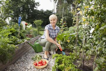 Deutschland, Nürnberg, Seniorin mit Gemüse im Garten