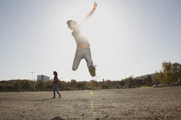 Deutschland, Köln, Mann springt im Feld, Frau, die im Hintergrund
