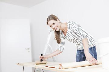Frau Anwendung Klebstoff auf Tapete