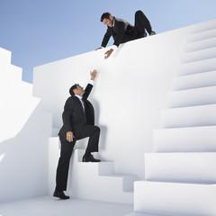 Geschäftsmann helfen, ein anderer Mann, Treppen zu steigen