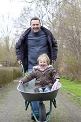 Deutschland, Vater Tochter schieben auf Schubkarre