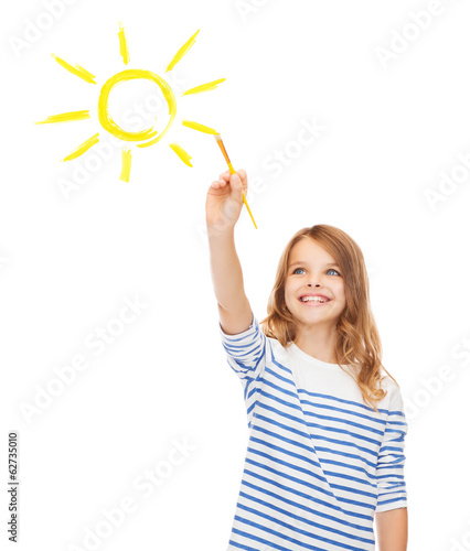cute little girl drawing sun with brush