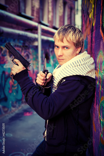 Blond teenager holding a pistol and knife at the graffiti wall